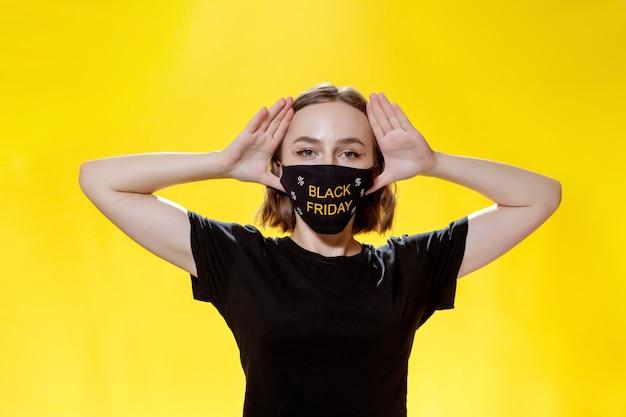 Frau in gesichtsmaske mit einkaufstüten am black friday in den händen. verkauf während der pandemie. konzept des schwarzen freitags.