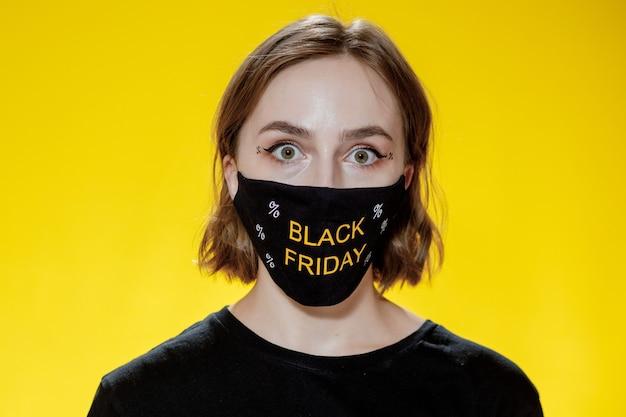 Frau in gesichtsmaske mit einkaufstüten am schwarzen freitag im handverkauf während der pandemie
