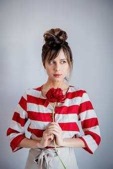 Frau in gestreiftem hemd rote pfingstrose durchlöchernd