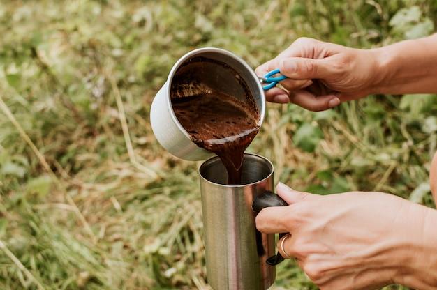Frau in gießt heißen kaffee in die schale