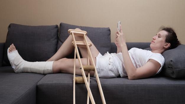 Frau in gips liegt zu hause auf der couch und benutzt smartphone.