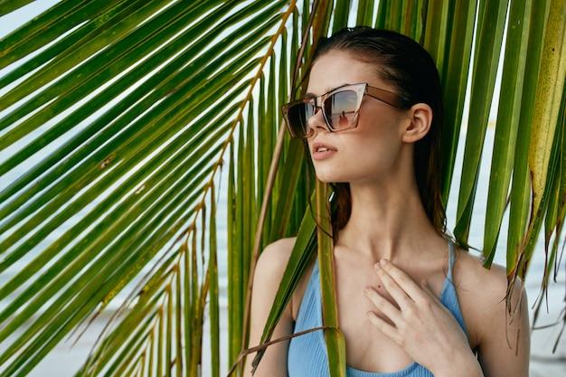 Frau in gläsern auf einem hintergrund von palmen