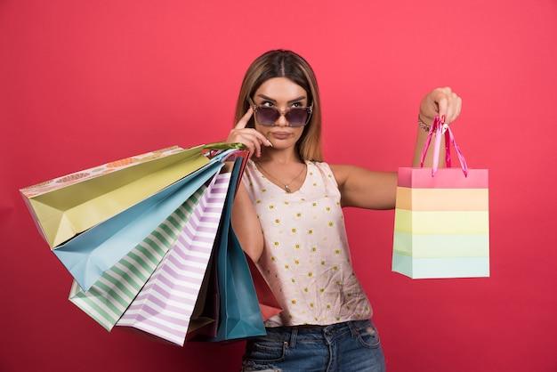 Frau in gläsern, die ihre einkaufstaschen an der roten wand halten.