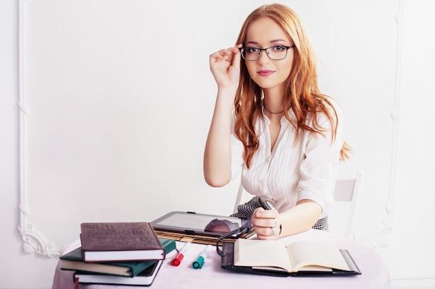 Frau in gläsern mit der tablette und dem notizbuch.