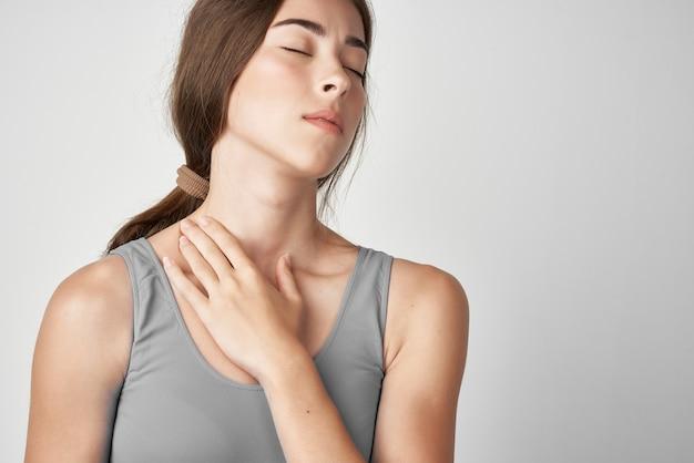 Frau in grauem t-shirt und gelenkschmerzen gesundheitsprobleme heller hintergrund. foto in hoher qualität