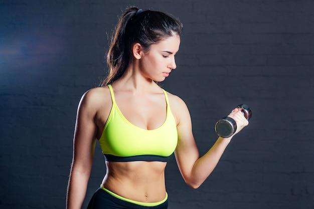 Frau in grünem sport-bh, die in einem fitnessstudio mit hanteln auf einem hintergrund aus schwarzen ziegeln beschäftigt ist