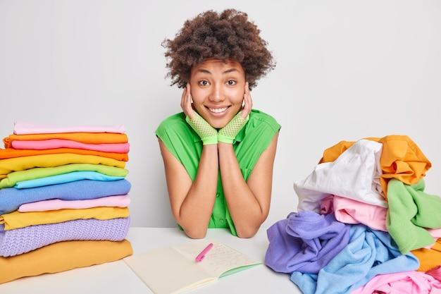 Frau in grüner bluse sitzt am tisch faltet kleidung nach dem waschen und trocknen macht sich notizen im notizblock schreibt liste für wochenenden auf, die damit beschäftigt sind, hausarbeit zu erledigen. hausarbeiten