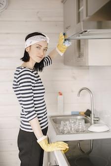Frau in gummihandschuhen, die die küche reinigen.