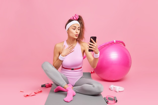 Frau in guter körperlicher verfassung macht videoanrufe hält smartphone-posen auf fitnessmatte macht pause nach dem training verwendet sportgeräte