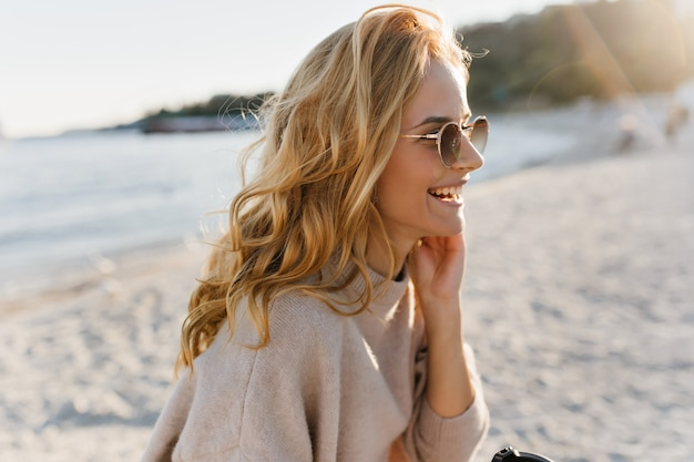 Frau in guter stimmung genießt sonnigen frühlingstag auf see. blinde im kaschmir-outfit mit einer tasse tee.