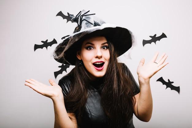 Frau in halloween hut mit den händen auseinander