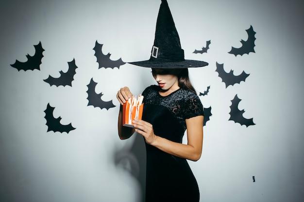 Frau in halloween hut mit lebensmittel-box