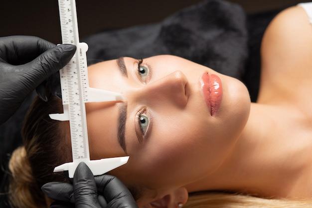 Frau in handschuhen bereitet sich mit einem lineal auf das permanente make-up der stirn vor