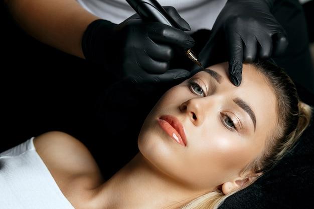 Frau in handschuhen, die einer hübschen blonden frau im kosmetiksalon permanentes brauen-make-up macht. ansicht von oben