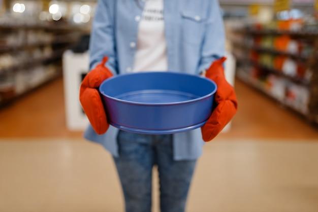 Frau in handschuhen hält schüssel, haushaltswarenladen. weibliche person, die haushaltswaren im markt kauft, dame im küchengeschirrversorgungsgeschäft