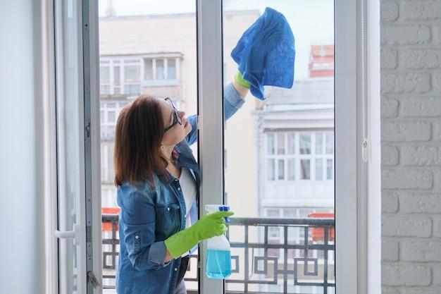 Frau in handschuhen mit mikrofaserlappen, der mit sauberem glasfenster des reinigungsmittels besprüht wird