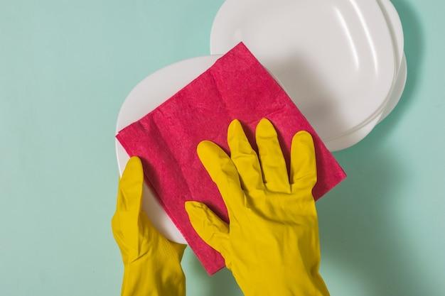 Frau in handschuhen wischt das geschirr nach dem waschen ab.