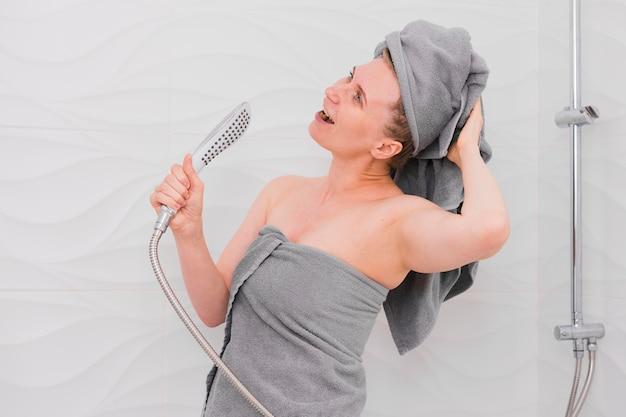 Frau in handtüchern, die im duschkopf singen