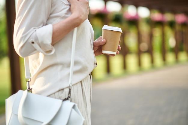 Frau in heller kleidung mit einem glas kaffee.