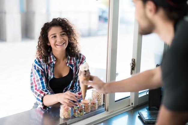 Frau in hemd-kaufender eiscreme im nahrungsmittel-lkw.