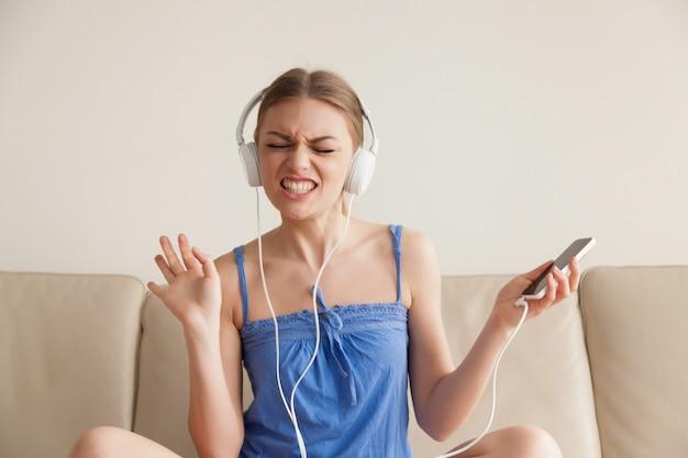 Frau in hörender musik der kopfhörer vom mobiltelefon