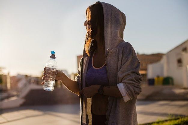 Frau in hoodie halten flasche mit wasser