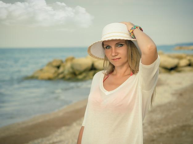 Frau in hut mit bunten armbändern am strand.
