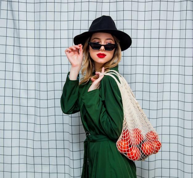 Frau in hut und grünem mantel im 90er stil mit netztasche