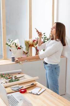 Frau in ihrem blumenladen, der ihr telefon betrachtet