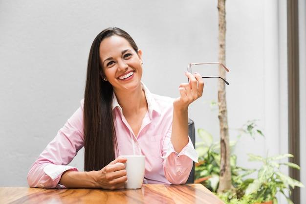 Frau in ihrem büro mit einem tasse kaffee