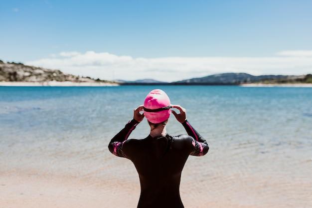Frau in ihren 40ern, die ein neopren trägt und wartet, um im see zu schwimmen. triathlon-konzept