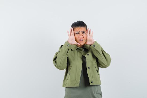 Frau in jacke, t-shirt händchen haltend im gesicht und verwirrt