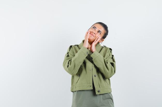 Frau in jacke, t-shirt händchen haltend in der nähe des mundes und hübsch aussehend