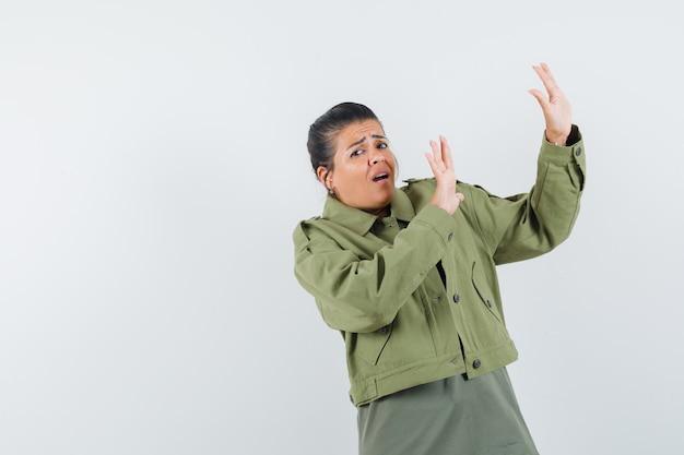 Frau in jacke, t-shirt händchen haltend, um sich zu verteidigen und ängstlich auszusehen
