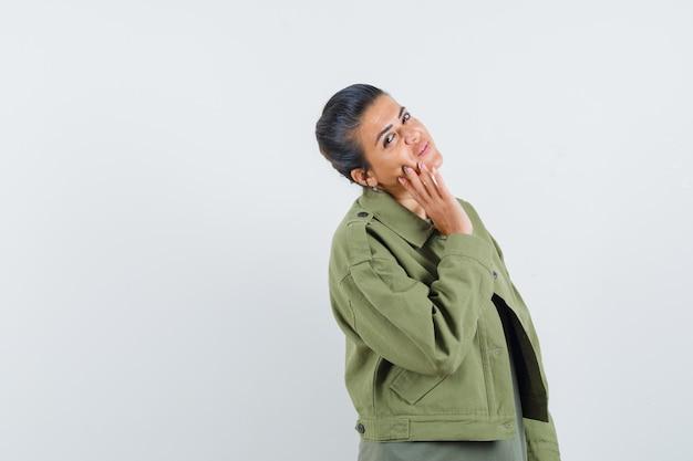 Frau in jacke, t-shirt posiert mit der hand auf der wange und sieht charmant aus