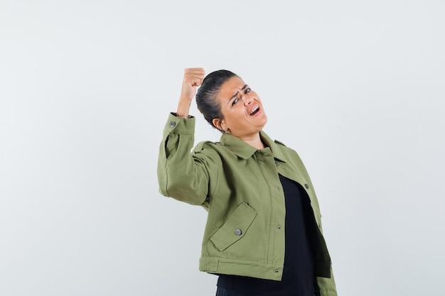 Frau in jacke, t-shirt zeigt siegergeste und sieht fröhlich aus