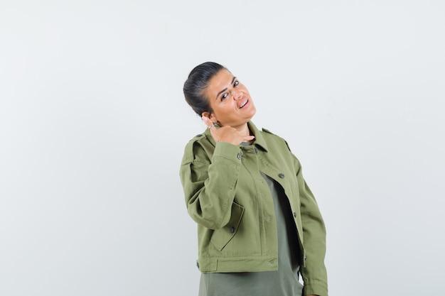 Frau in jacke, t-shirt zeigt telefongeste und sieht selbstbewusst aus