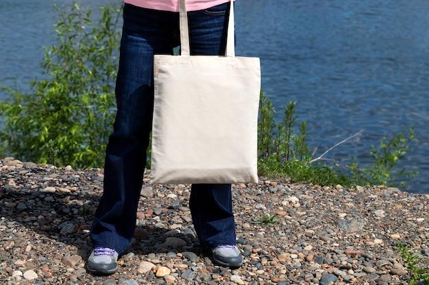 Frau in jeans, die leeres wiederverwendbares einkaufstaschenmodell trägt.