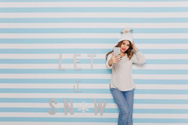 Frau in jeans, die selfie neben winterinschrift nimmt: lassen sie es schneien