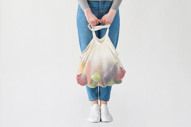 Frau in jeans, die wiederverwendbare tasche mit lebensmitteln hält
