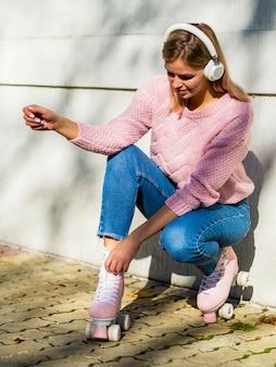 Frau in jeans mit rollschuhen und kopfhörern