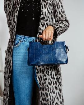 Frau in jeans, schwarzem top und strickjacke mit leopardenmuster, die dunkelblaue tasche hält