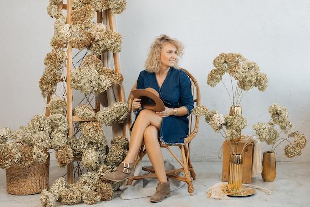 Frau in jeanskleid und ausgefallenen stiefeln, glücklich mit der geleisteten arbeit, dekorationsraum im studio für aufnahmen, trockene hortensien, holztreppen, körbe, vasen. natürliches dekor