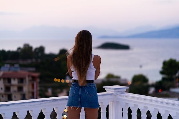 Frau in jeansshorts, die auf dem balkon stehen und den meerblick und den schönen sonnenuntergang betrachten. urlaub auf tropischer insel. luxus-lebenskonzept. entspannen.