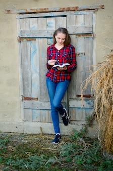 Frau in kariertem hemd und jeans liest ein buch mit dem rücken zur tür