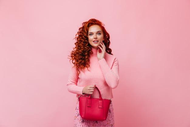 Frau in kaschmirpullover und geblümtem rock hält tasche und schaut in die kamera gegen rosa wand