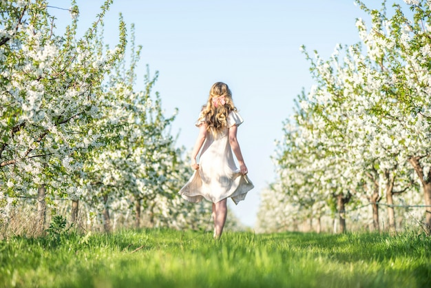 Frau in kirschblühendem obstgarten im frühjahr
