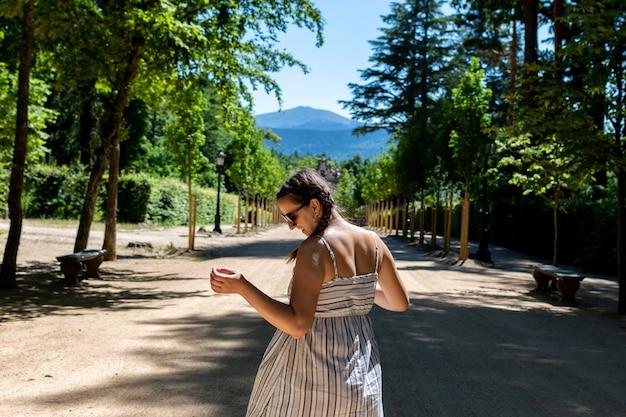 Frau in kleid und sonnenbrille zu fuß durch die gärten des palastes von granja de san idelfonso.