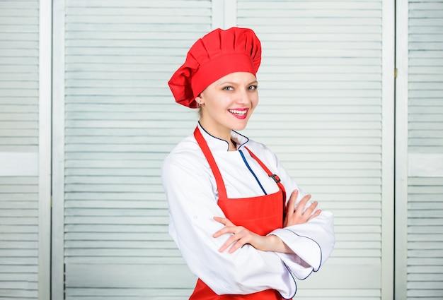 Frau in kochmütze und schürze. professioneller koch in der küche. küche. glückliche frau, die gesundes essen nach rezept kocht. hausfrau mit kochutensilien. hilfreiche technik. präsentation von speisen.