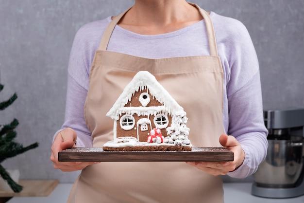 Frau in küchenschürze hält tablett mit lebkuchenhaus. silvester backen.